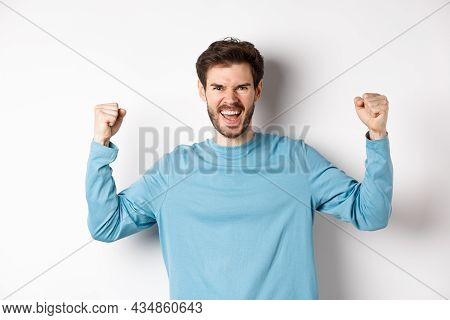 Portrait Of Satisfied Handsome Man Winning Prize, Rejoicing In Triumph, Celebrating Victory And Shou