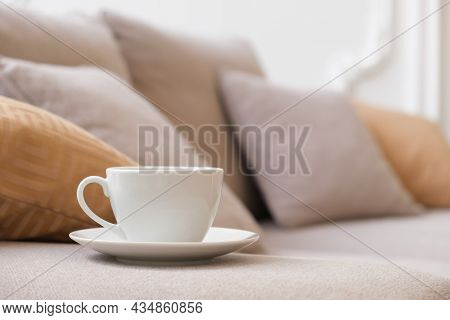 White Coffee Cup And Saucer Sits On The Arm Of The Living Room Sofa On The Background Of A White Wal