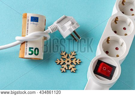 White Electric Plug Tied To A Knot On A Fifty Euro Banknotes, Snowflake And Power Strip Over Blue Ba