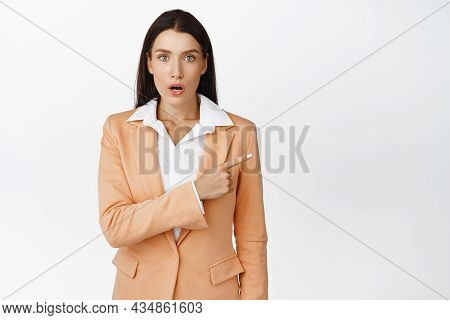 Surprised Brunette Businesswoman Pointing Right, Looking Amazed At Camera, Gasping And Staring In Aw