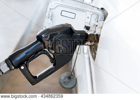 Nozzles In The Gas Station. A Diesel Dispenser That Is Filling Up With A Car That Stops For Fuel Dur