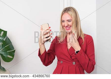 Young Blonde Woman In Business Red Dress Looks At The Screen Of Smartphone On Heroutstretched Hand T