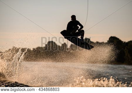 Silhouette Of Man Rider Skilfully Making Jump And Trick On Wakeboard. Watersports Activity