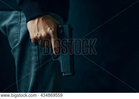 Man Stands With Gun Lowered. Person In Jeans Holds Firearm In His Hand. Criminal With A Revolver. At