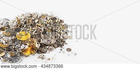Gears, Clock Faces And Metal Parts Of Internal Mechanism Of The Watch Lie In Heap On White Backgroun