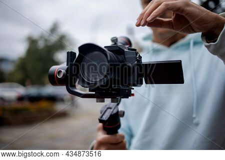Young Professional Videographer Holding Professional Camera On 3-axis Gimbal Stabilizer. Pro Equipme