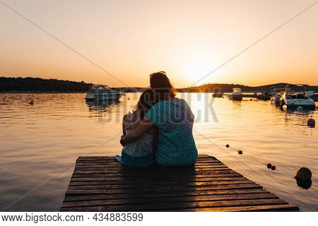 Mom And Daughter Sitting On A Wooden Pier, Hugging Each Other Admiring The Setting Sun Over The Sea