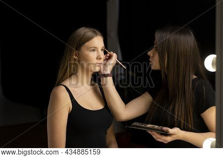 Makeup Artist Doing A Eyebrows Makeup On A Beautiful Woman Face. Hand Of Make-up Master Is Painting