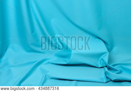 Textured Background Made Of Soft Blue Fabric With Elegant Pleats.