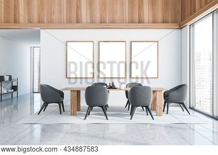 Three Empty Frames In The White Dining Room Interior With Wood Materials, Dark Grey Chairs, A Table