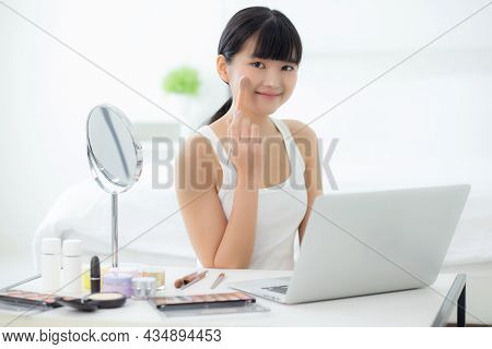 Beauty Of Young Asian Woman With Learning Makeup With Brush On Cheek On Laptop Computer With Tutoria
