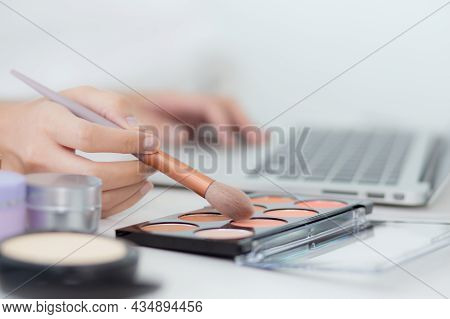 Hands Of Woman With Learning Makeup With Brush On Cheek On Laptop Computer With Tutorial Course Onli