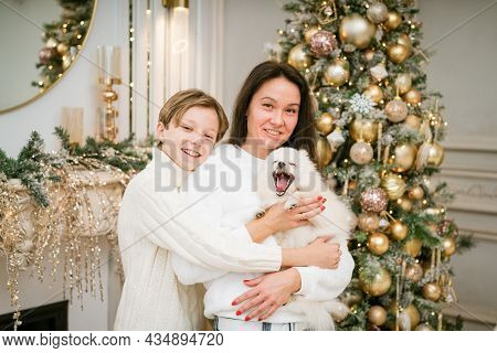 Beautiful Smiling Mom And Son Hugging With A Happy White Dog At Home For Christmas Vacation. Happy F