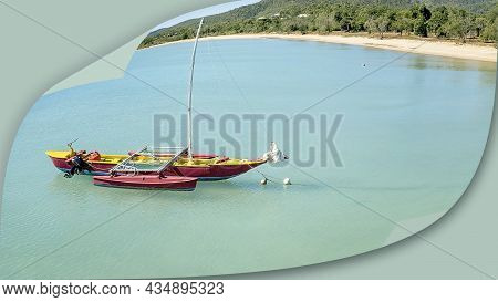 A Red And Yellow Boat Anchored Off Shore With Mast Down On Calm Aqua Sea On Sandy Beach Coastline. P