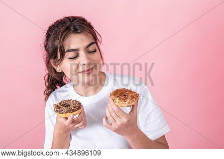 Funny Cute Young Beautiful Girl Dressed A White T-shirt Holds Two Sweet Baked Donuts, Is Isolated On