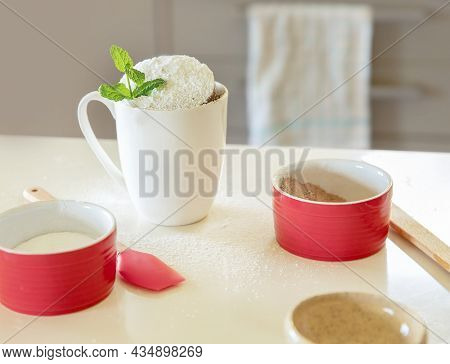 cake in a mug in white cup, baking ingredients on white kitchen table, baking at home with kids, dessert preparation.