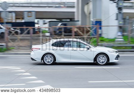 Toyota Camry Xv70 At High Speed. Fast Moving Toyota Camry Rides On City Highway. Side View Of Car On