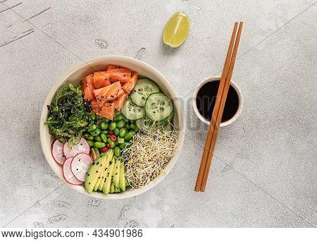 Healthy Poke Bowl With Salmon, Avocado, Edamame Beans, Cucumber, Radish, And Seaweed, Top View. Hawa