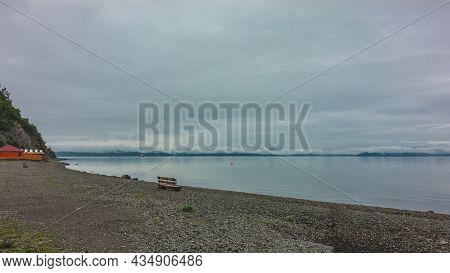Pacific Ocean Coast. Cloudy. There Is A Lonely Wooden Bench On The Pebble Beach.  Cumulus Clouds Are