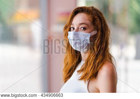 Young Red Haired Woman With A Surgery Mask, Protection And Precaution For Contagious Disease. Corona