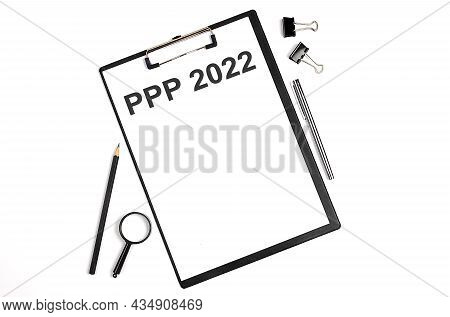 On A White Background Magnifier, A Pen And A Sheet Of Paper With The Text Ppp 2022 . Business