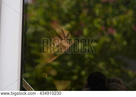 Young Woman In Black Medical Mask Looking Out Window Being Isolated At Home During Coronavirus Epide