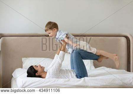 Happy Mixed Race Family Doing Balance Exercises In Bedroom.