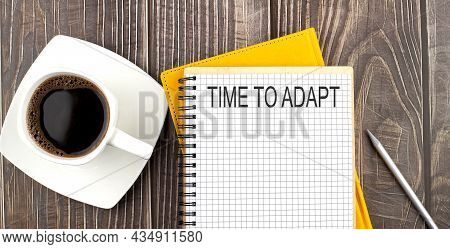 Time To Adapt Text On The Notebook With Coffee On The Wooden Background