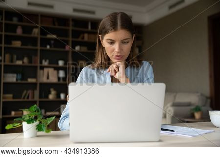 Serious Pensive Young Employee Working At Laptop From Home