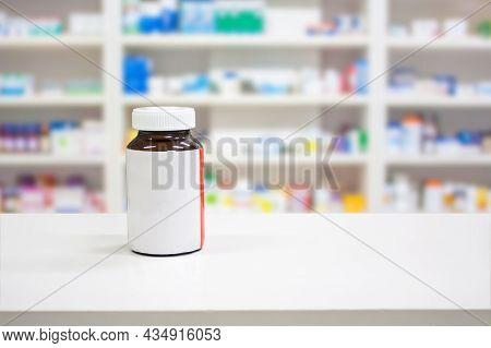 Blank White Label Medicine Bottle On Counter With Blur Shelves Of Drug In The Pharmacy Drugstore