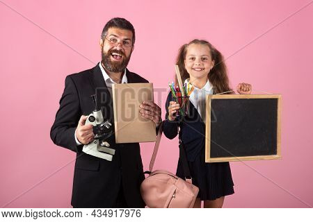 Schoolkid Girl Pupil And A Teacher On Pink Studio Background.