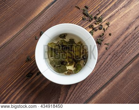 Green Tea Is Brewed In A White Bowl On A Wooden Background. Dry Tea Leaves Lie Nearby. Top View