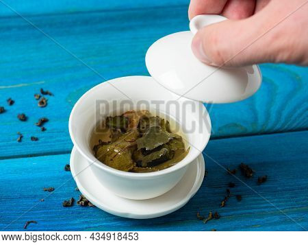 A Bowl Of Brewed Tea On A Blue Wooden Background. A Hand Lifts The Lid Of The Bowl. The Opened Leave