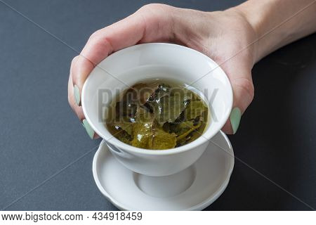 A Woman's Hand Holds A White Porcelain Bowl With Tea. Dark Background. The Opened Leaves Of Large-le