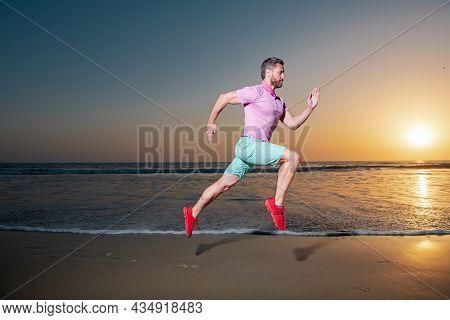 Man Running On The Beach At Sunset. Sport And Healthy Lifestyle. Athlete Running Around The Beach Li