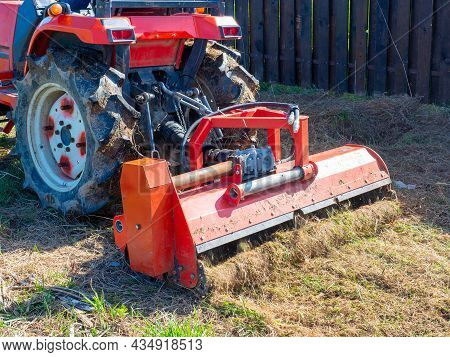 Close-up Of A Tractor With A Chain Mower Chopping Dry Grass. Maintenance Of The Territory, Mulching