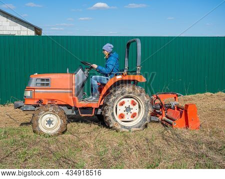 The Girl Sits In A Small Tractor And Drives Through The Field Mulching Grass. Land Cultivation, Agro