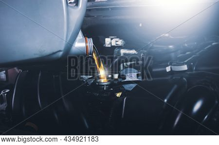 Mechanic Pouring Oil Lubricant Into The Car Engine For Vehicle Maintenance
