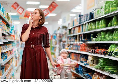 A Young Woman Chooses Products, Holding A Grocery Cart With A Baby Sitting In It. Indoor. The Concep