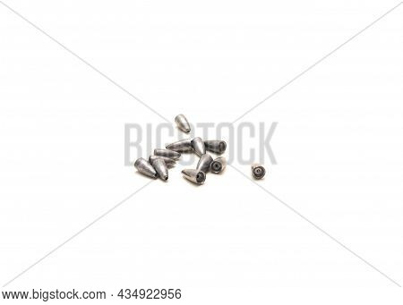 Pile Of Lead Bullet Weights With Concave Bases To Fit Worm Noses Isolated On White