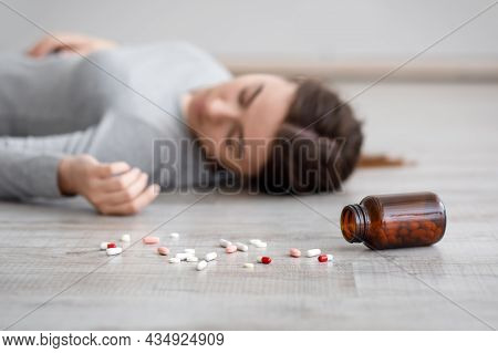 Caucasian Sad Millennial Woman Suffering From Depression Commits Suicide, Lies Unconscious, Focus On