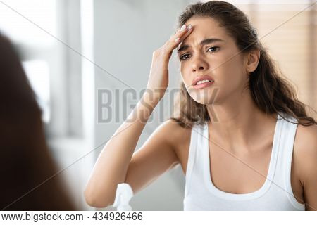 Unhappy Young Female Touching Forehead Looking At Wrinkles In Bathroom