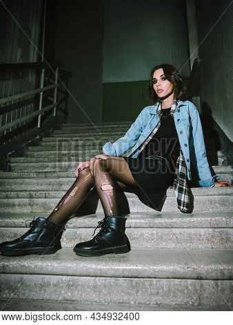 Indoor Portrait Of Cool Grunge (rock) Girl Sitting On The Stairway. Informal Model, Dressed In A Jea