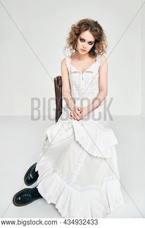 Portrait Of Attractive Strange Sad Girl. Beautiful Odd Young Woman In White Dress Sitting On Chair I
