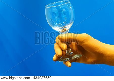 A Hand Prosthesis Made Of High-strength Plastic Holds A Glass Cup. Modern Technologies In The Field