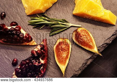 Fruits And Slices Of Hard Cheese On A Background Of Dark Stone Countertops. Still Life Of Healthy Pr