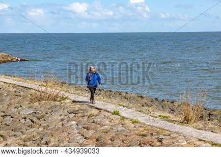 Female Tourist Walking On A Promenade With Her Mobile Phone Gimbal Tripod Head Stabilizer In Hand, B