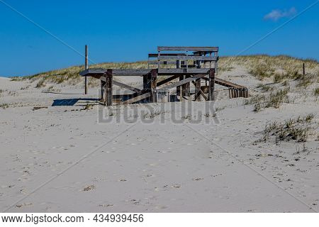 Beach With An Old Abandoned Wooden Structure With A Small Hill With Brown Grass In The Background, S
