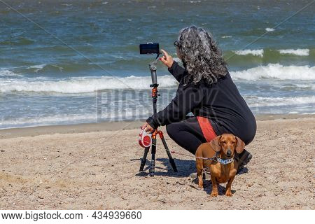 Mature Woman Squatting With Her Back To Camera On Renesse Beach Filming With Her Mobile Phone Gimbal
