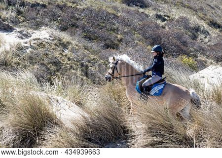 Renesse, Schouwen-duiveland, Zeeland Province, Netherlands. April 26, 2021. Young Female Rider With